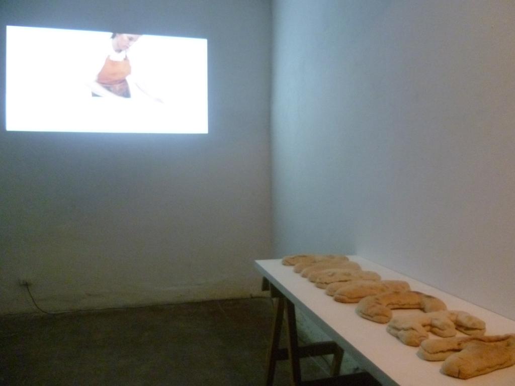 Vista de la exposición. Video proyección y palabra modelada en pan.